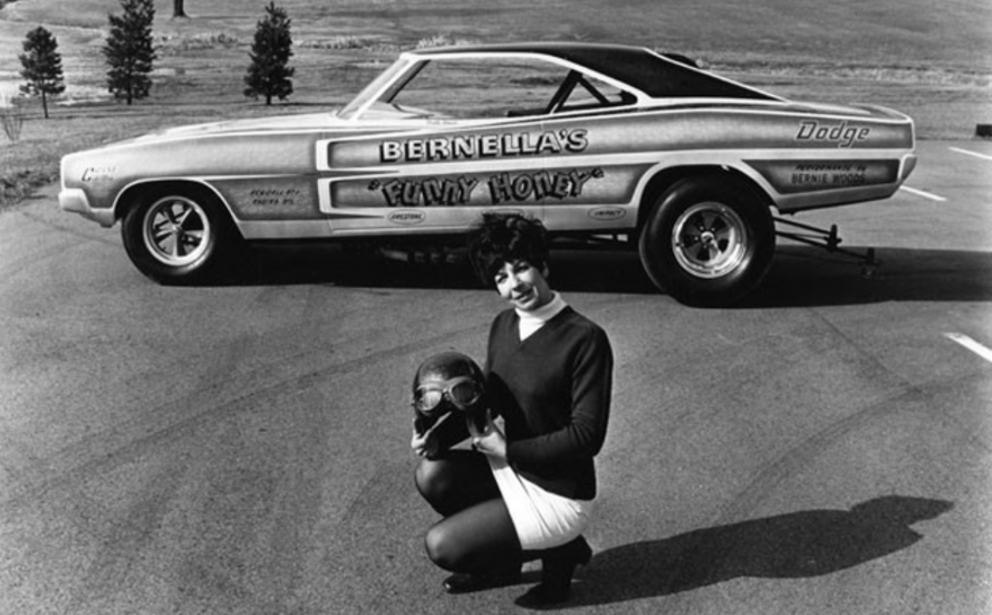 Person kneeling in front of a classic funny car