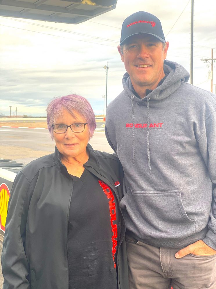Carolyn posing with Chris Jacobs at Bondurant