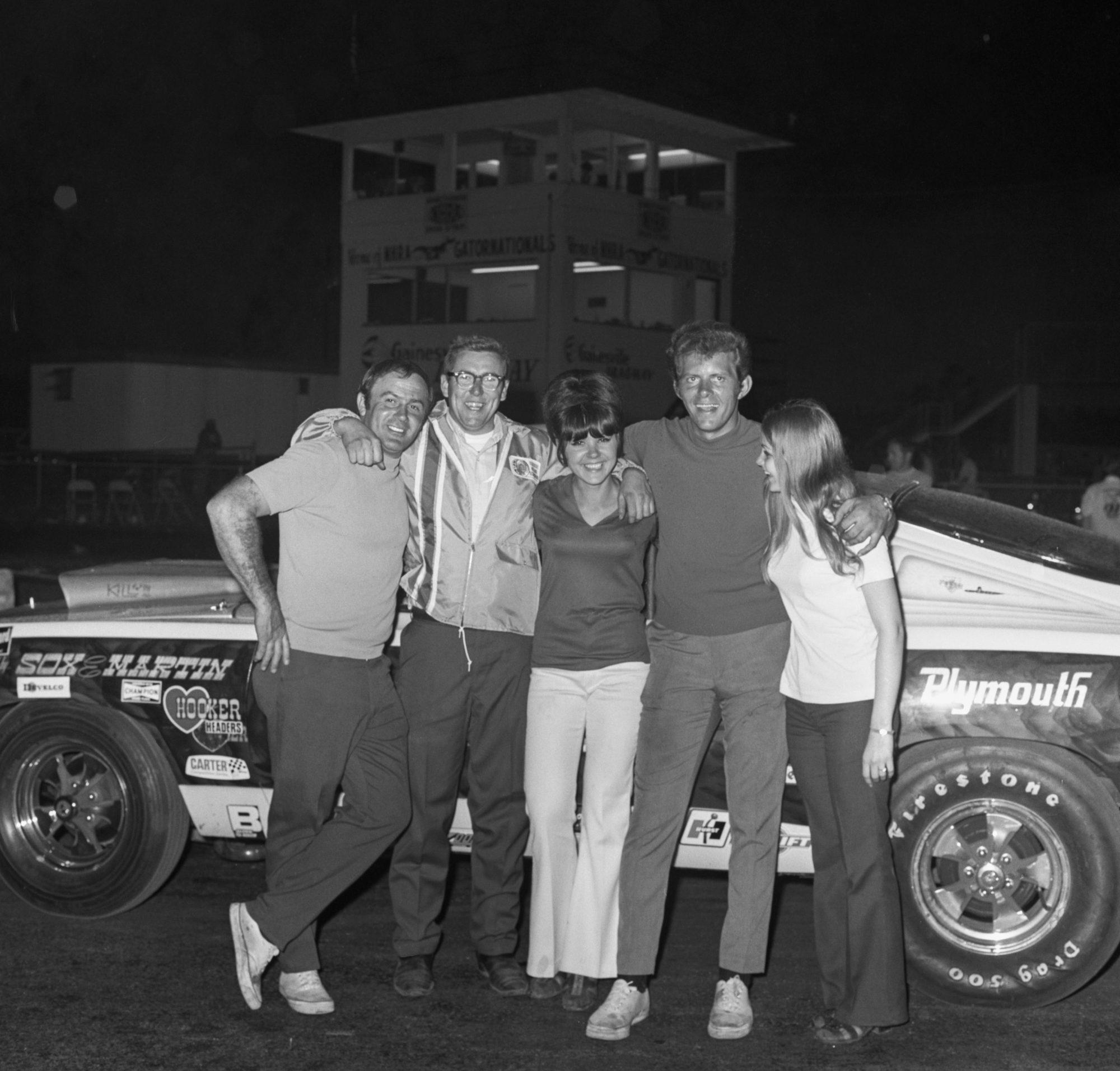 Herb McCandless posing with friends in front of his race car