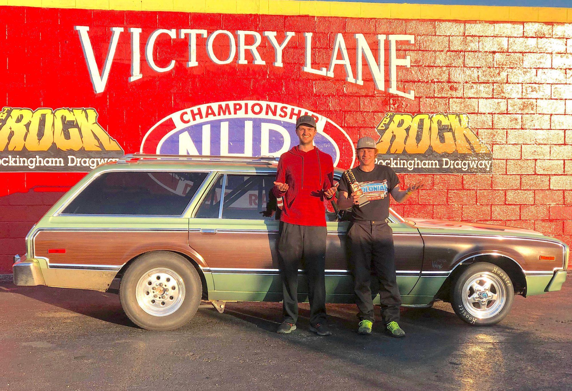 2 men standing next to a race car