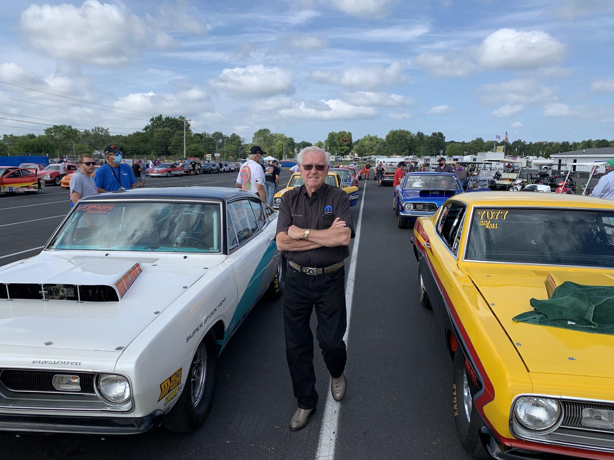 Herb McCandless posing next to race cars