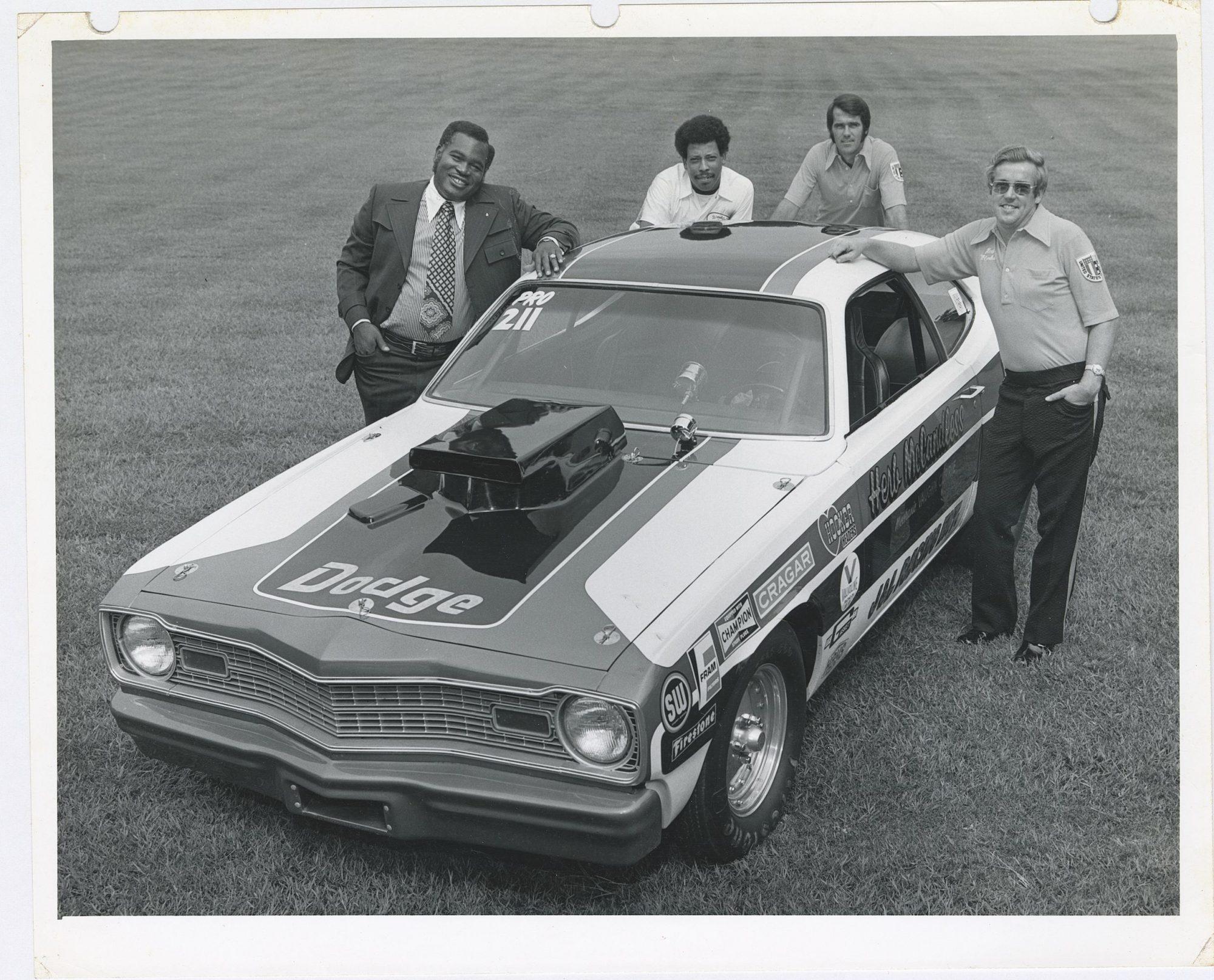 Herb McCandless posing next to his race car