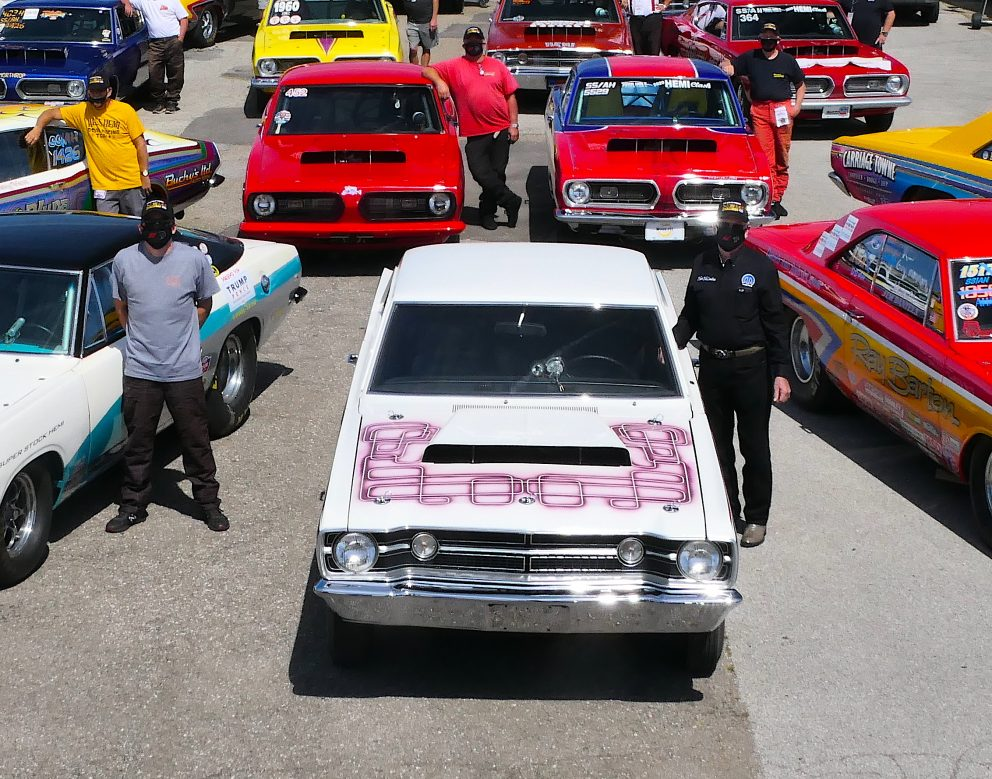 Men standing next to their race cars