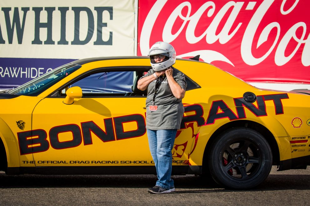 Carolyn putting on a helmet to race at Bondurant