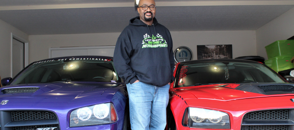 Anthony Carter standing next to his Dodge cars
