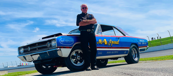 Herb McCandless standing next to his race car