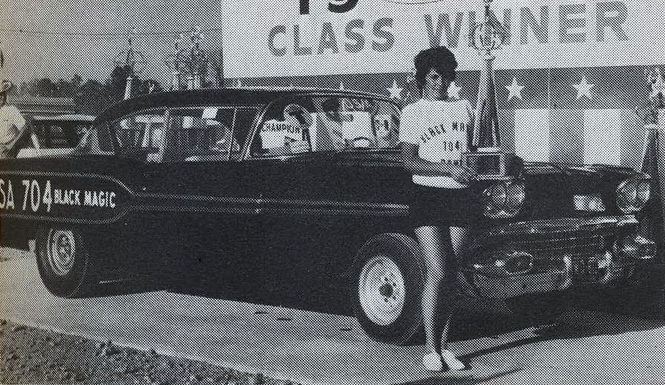 Mary Ann Foss holding a trophy while standing in front of her race car