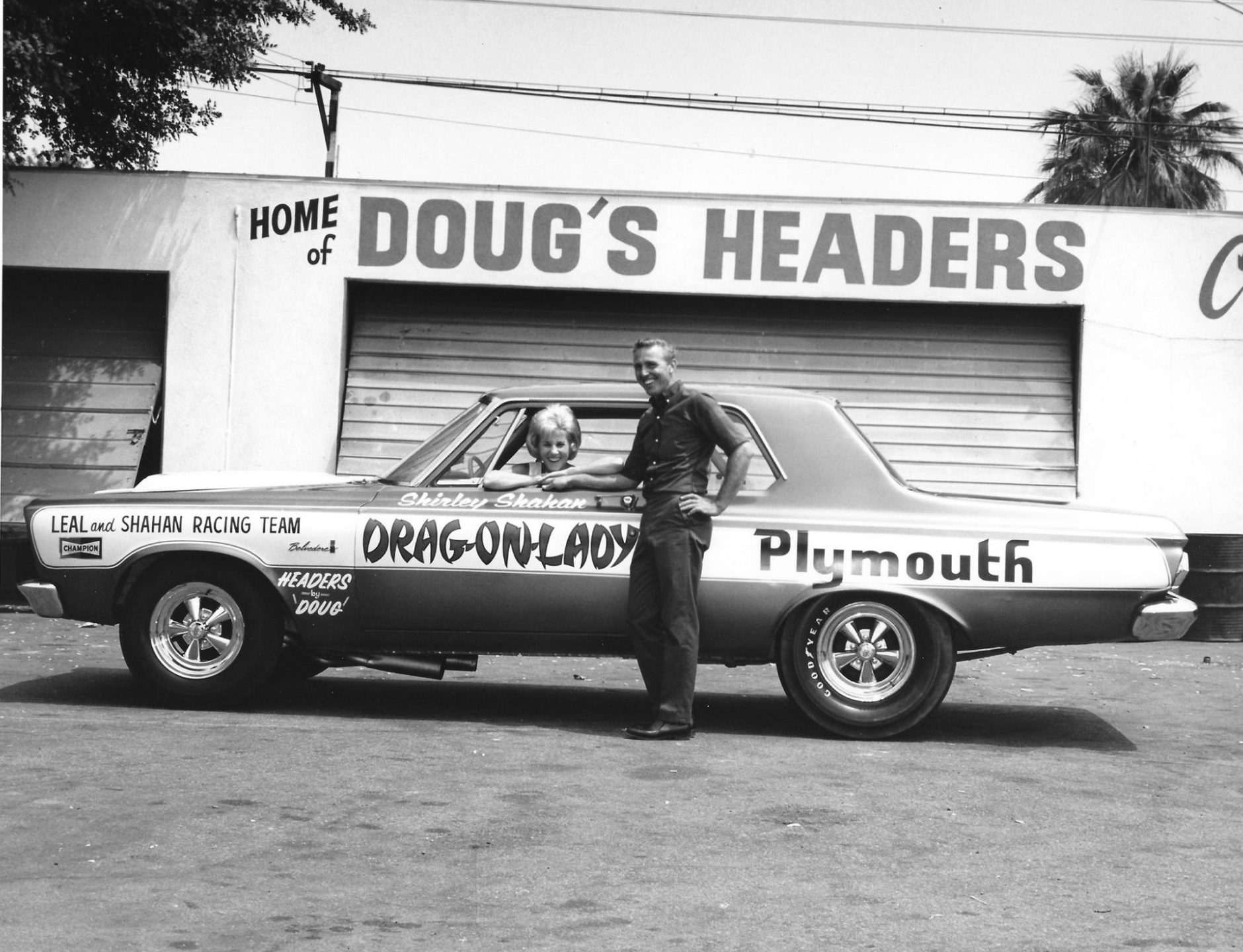 Shirley and H.L. posing with their drag car