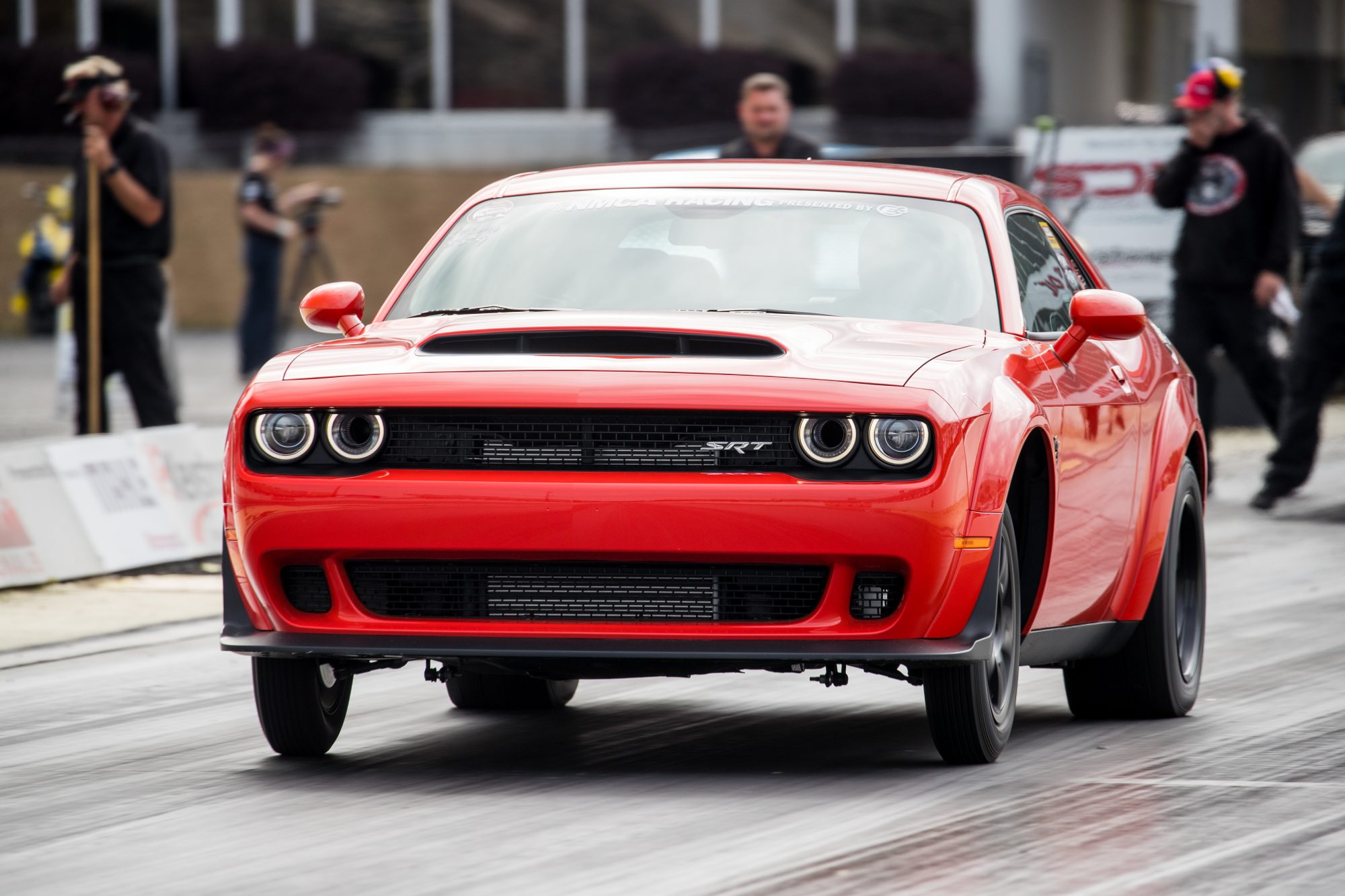Red Dodge Challenger drag racing at NMCA event