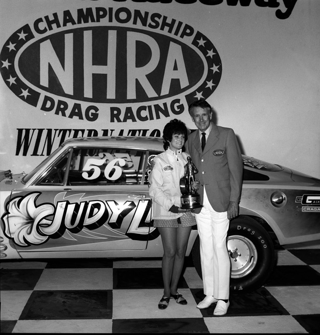 Judy Lilly holding a trophy in front of her drag car