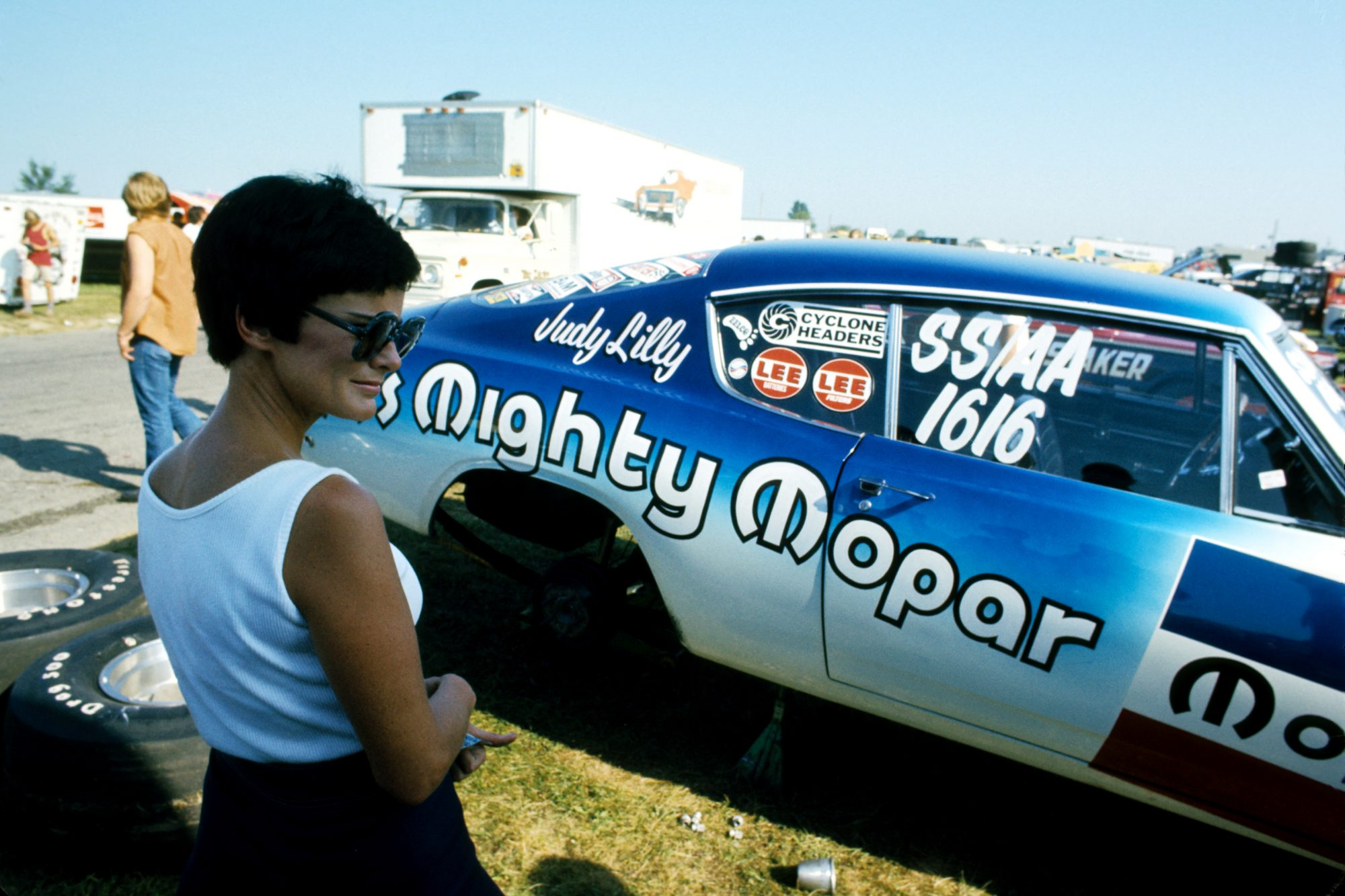 Judy Lilly standing outside of her drag car