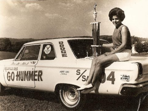 Mary Ann Foss sitting on the trunk of her race car holding a trophy