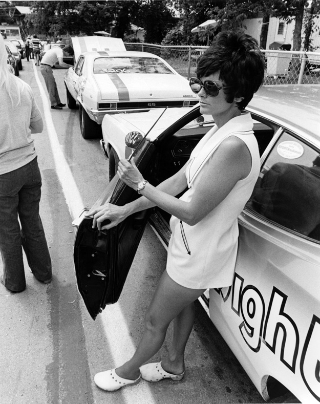 Judy Lilly standing outside of her drag car in the staging lanes