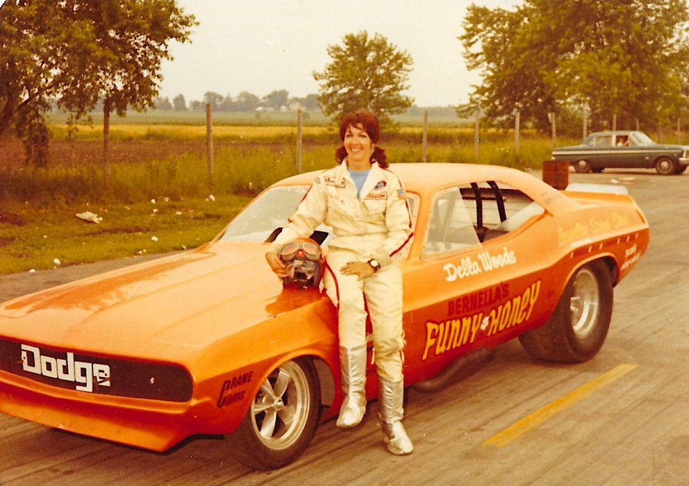 Della Woods posing with her race car