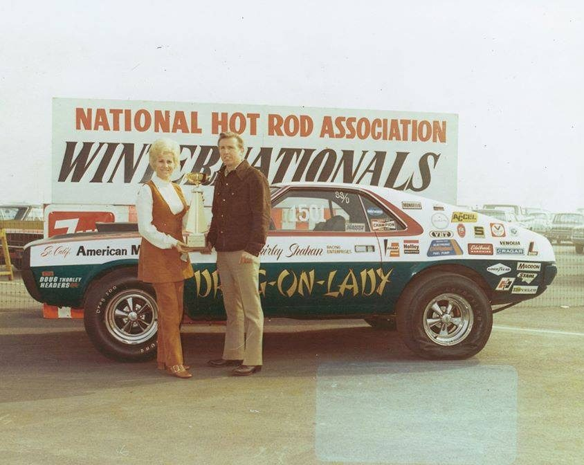 Shirley and H.L. holding a trophy in front of her drag car