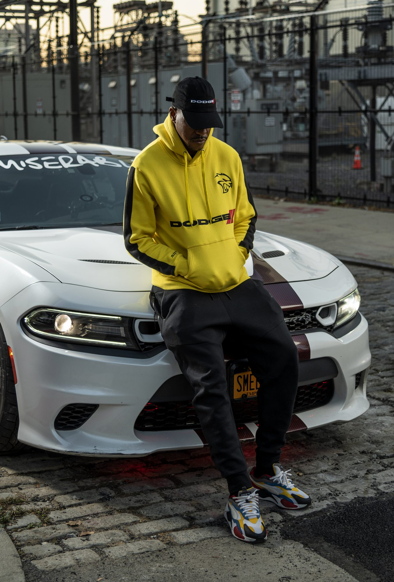 man wearing Dodge hoodie sitting on a Dodge Charger