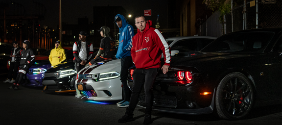 men standing next to Dodge cars wearing Dodge merchandise