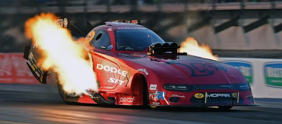 Funny Car with flames coming off it on a drag strip