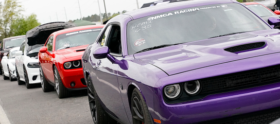 Line of Dodge Chargers and Challengers in the staging lanes at an NMCA race event