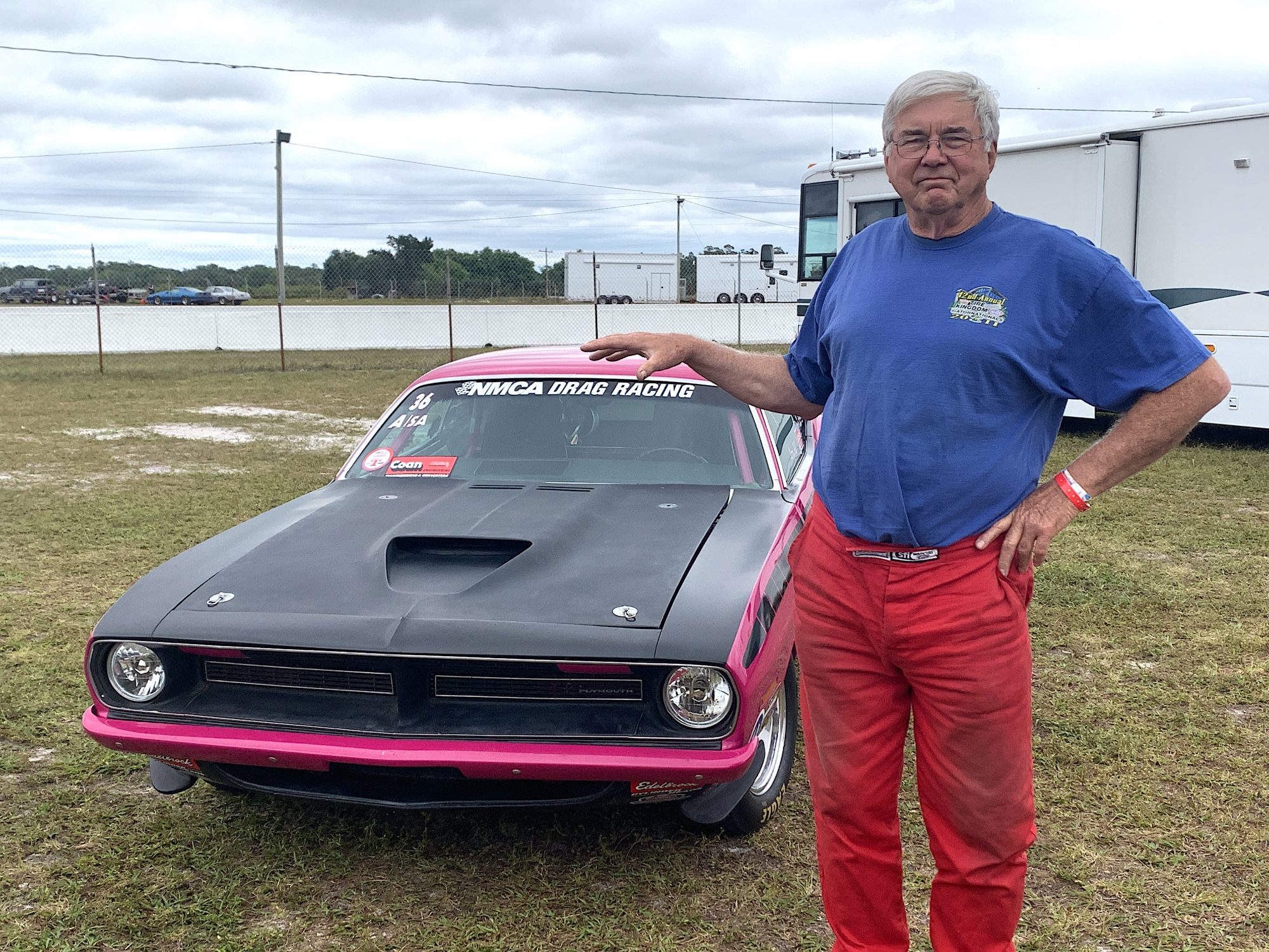 Larry Hill posing with his drag car
