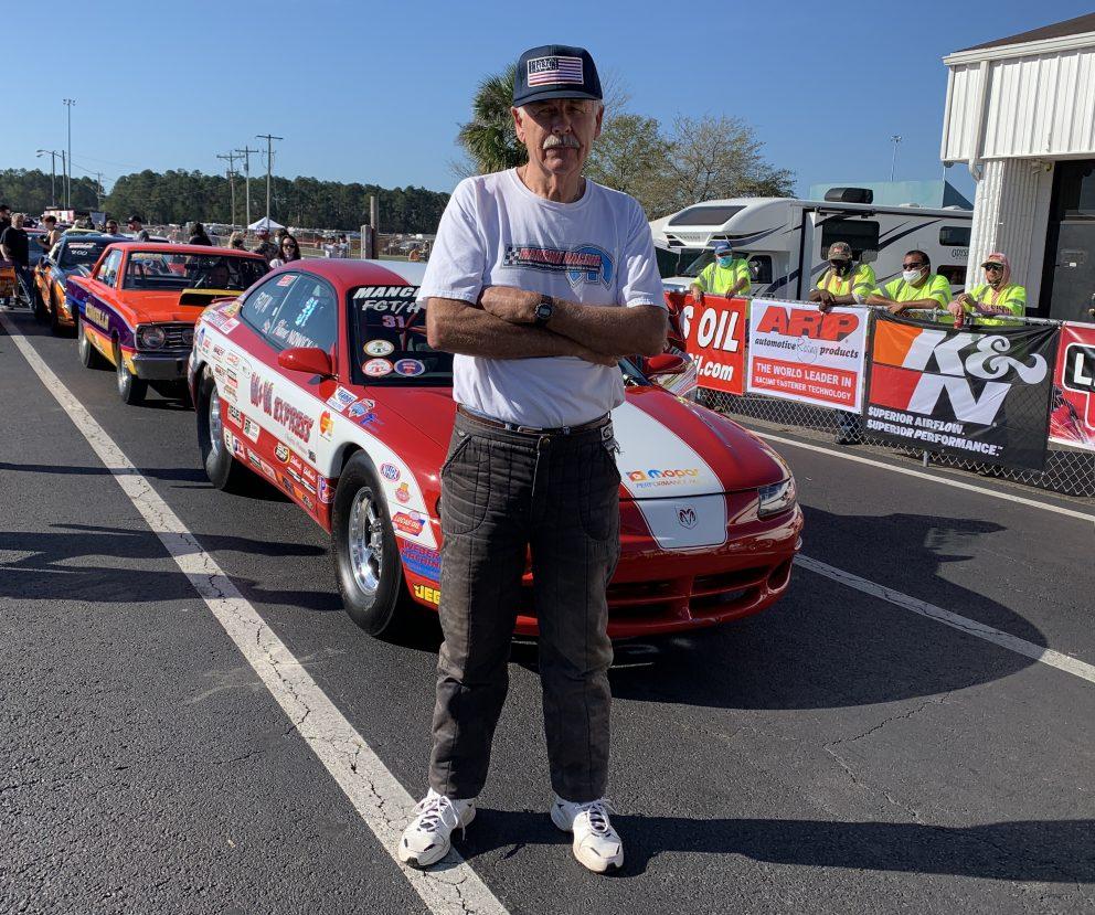 Mark Nowicki standing outside of his race car