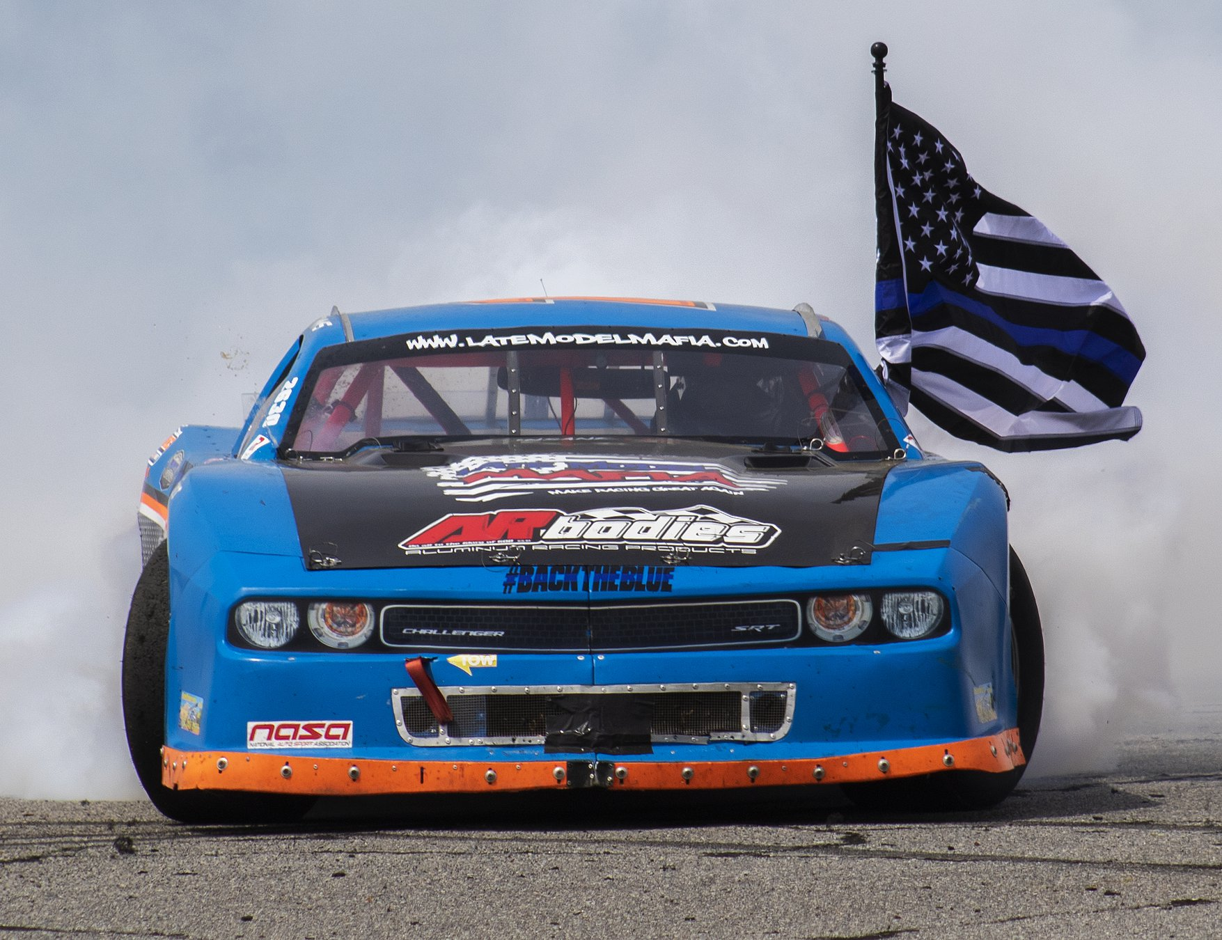 Challenger doing a burnout with a police flag