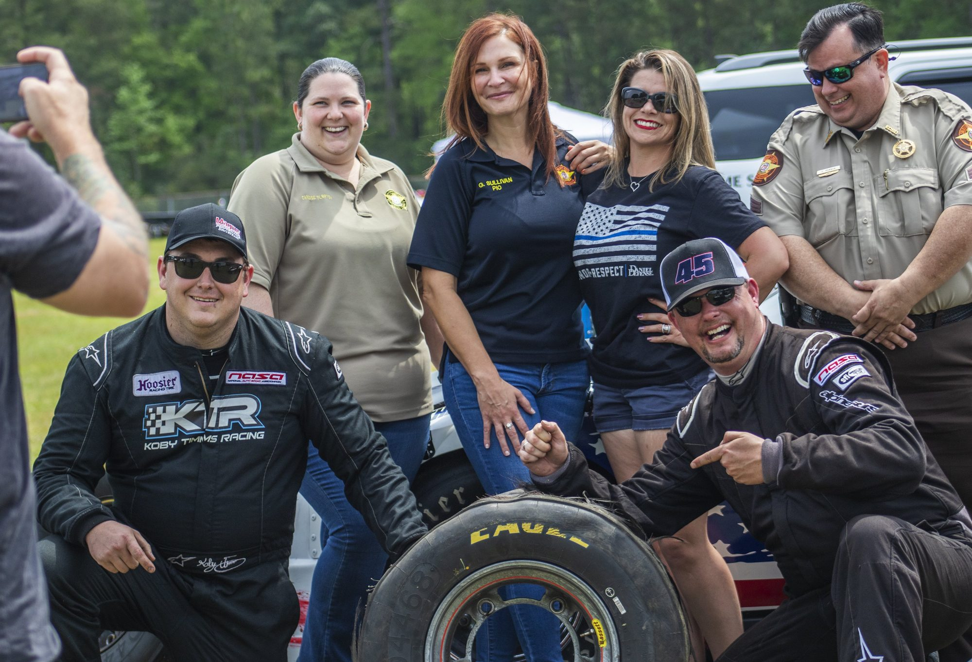 Group of people posing with blown out tire