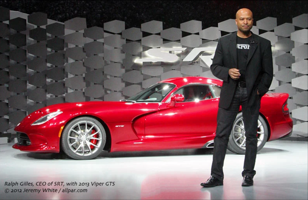 Ralph Gilles standing in front of the Viper wearing a Detroit shirt