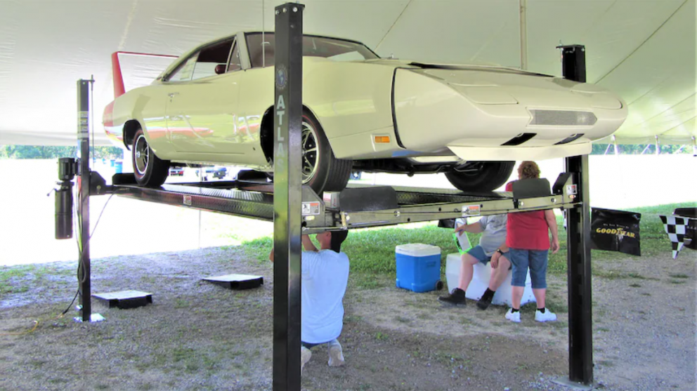 People working on a suspended 1969 Dodge Daytona