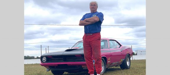 Larry Hill standing in front of his drag car