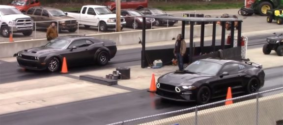 Ford Mustang GT and a Dodge Challenger SRT Hellcat Redeye on the starting line of a drag strip