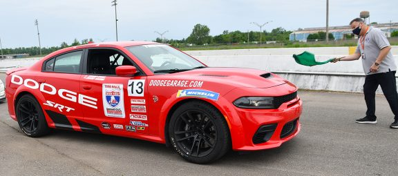 2021 Dodge Charger SRT® Hellcat Redeye on a starting line with a man and a green flag