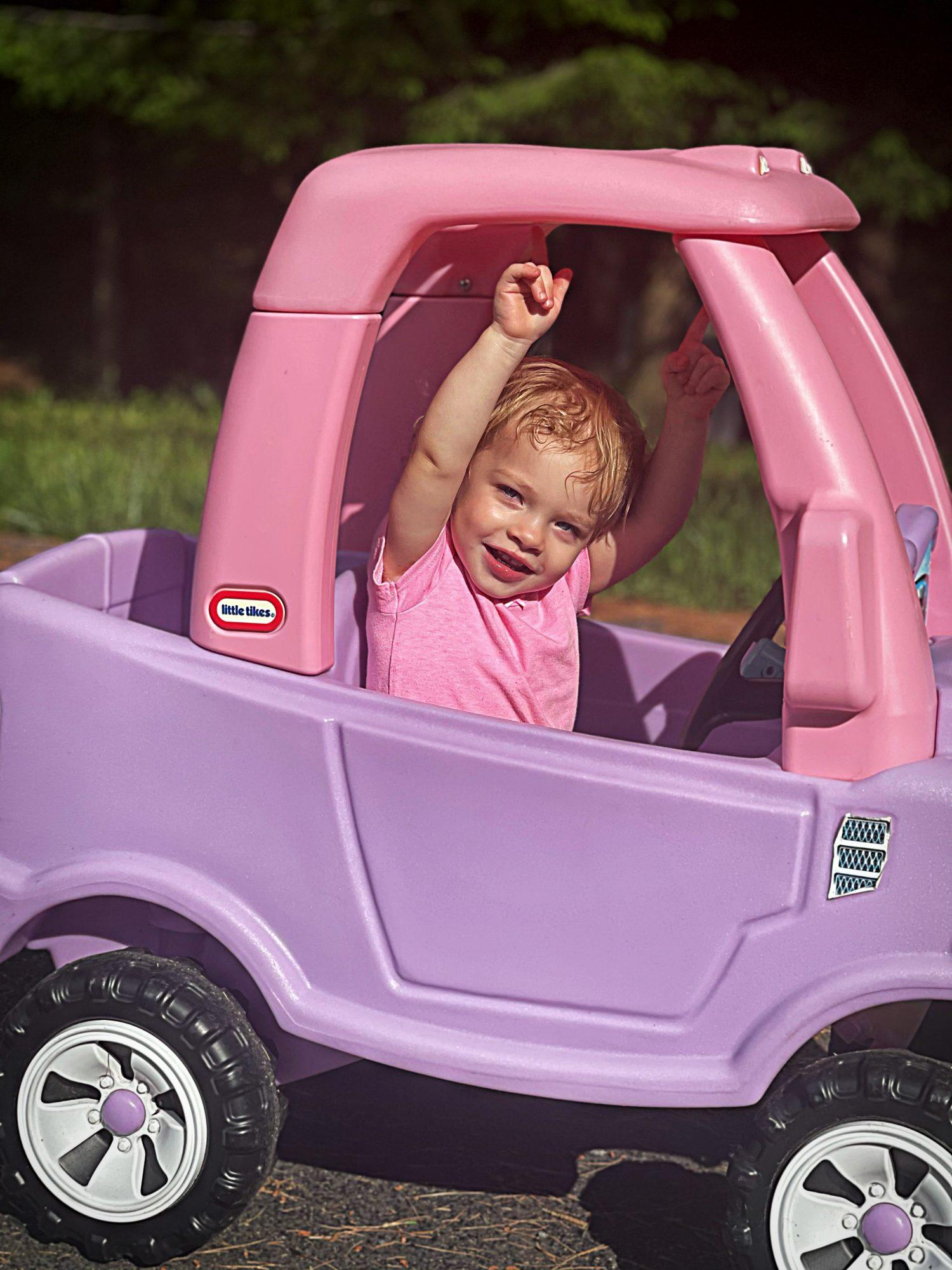 Leah Greenstein in her Little Tikes car
