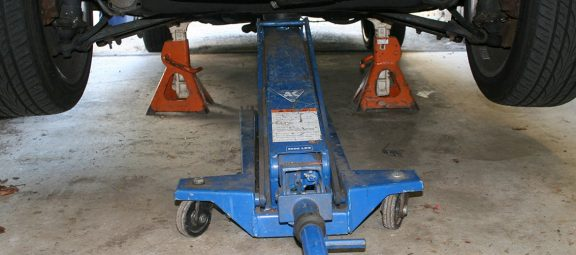 A car jack and jack stands holding up a vehicle