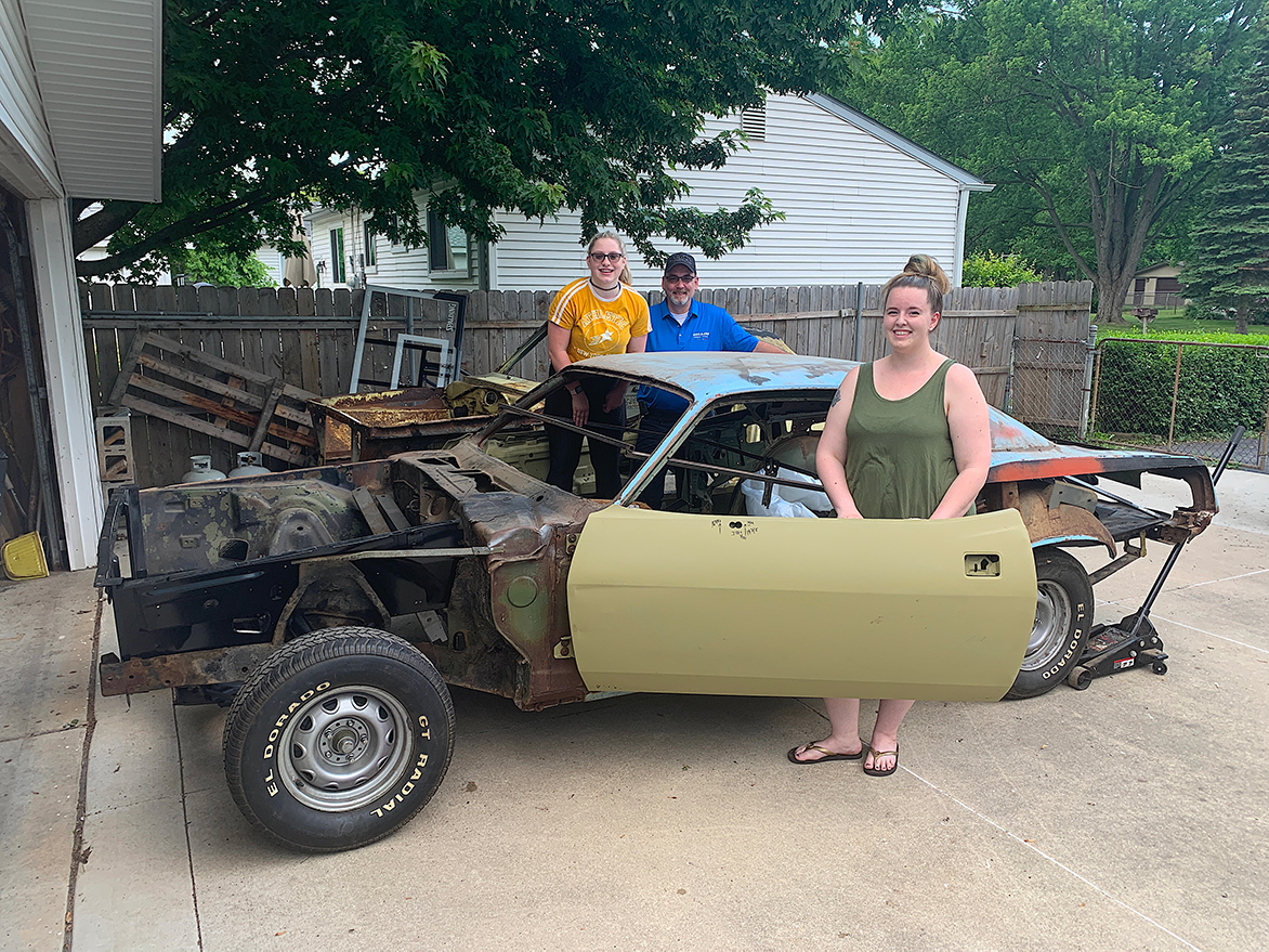 One man and two women with an old vehicle