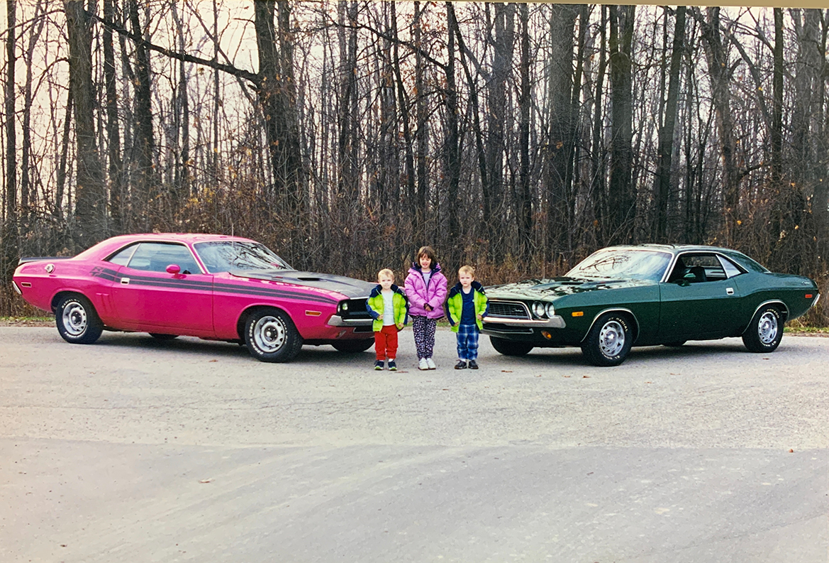 Old picture of three kids with two classic vehicles