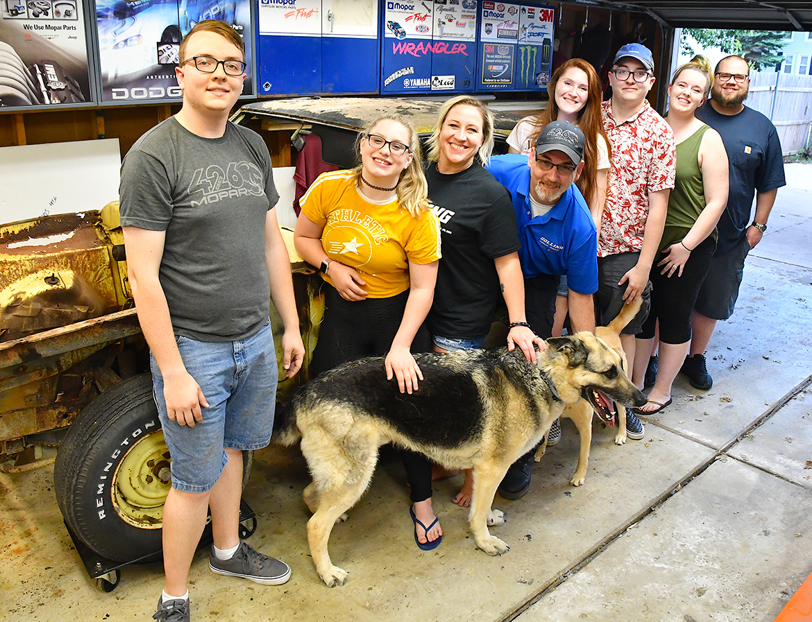 Four men, four women and one dog standing with an old vehicle in a garage