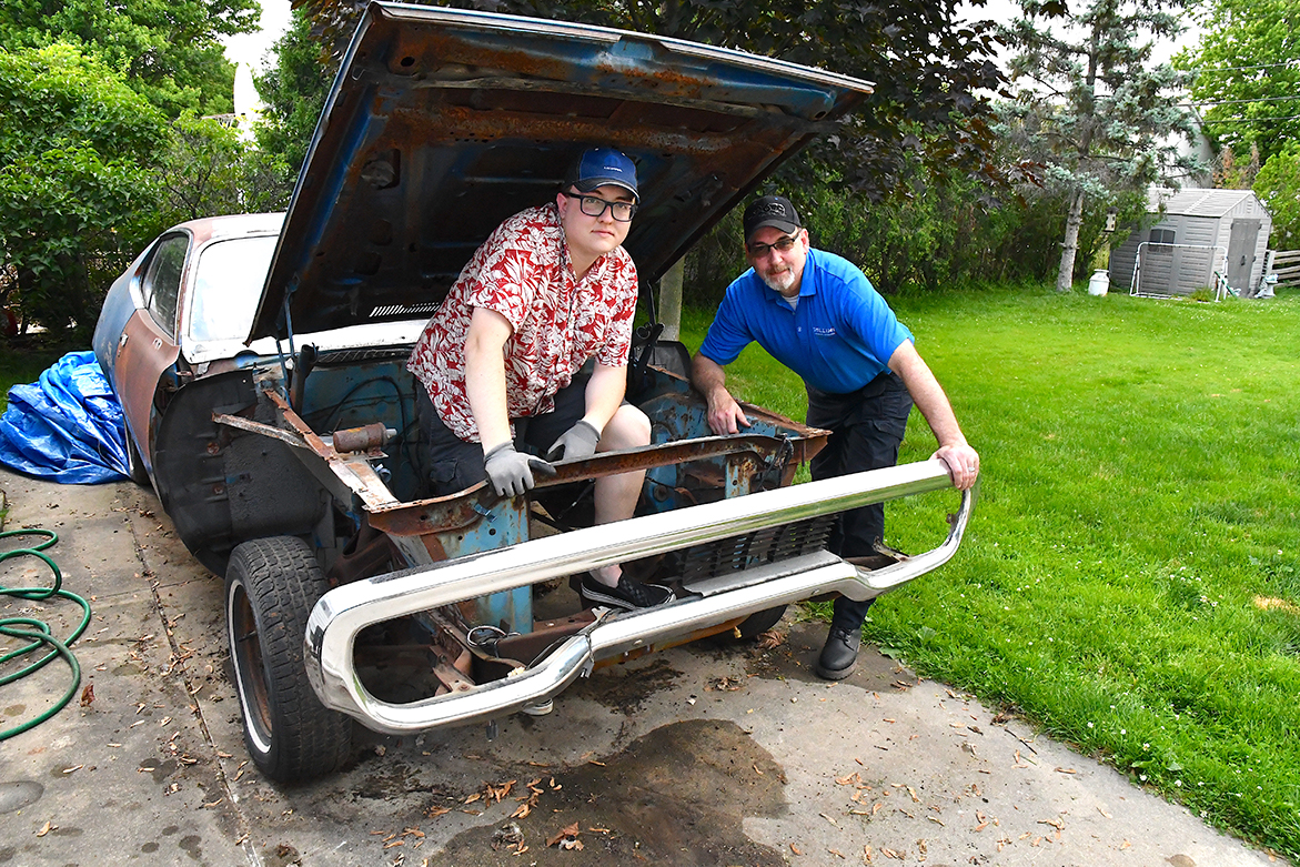 Two men with a rusted vehicle that has parts of the body missing and no engine
