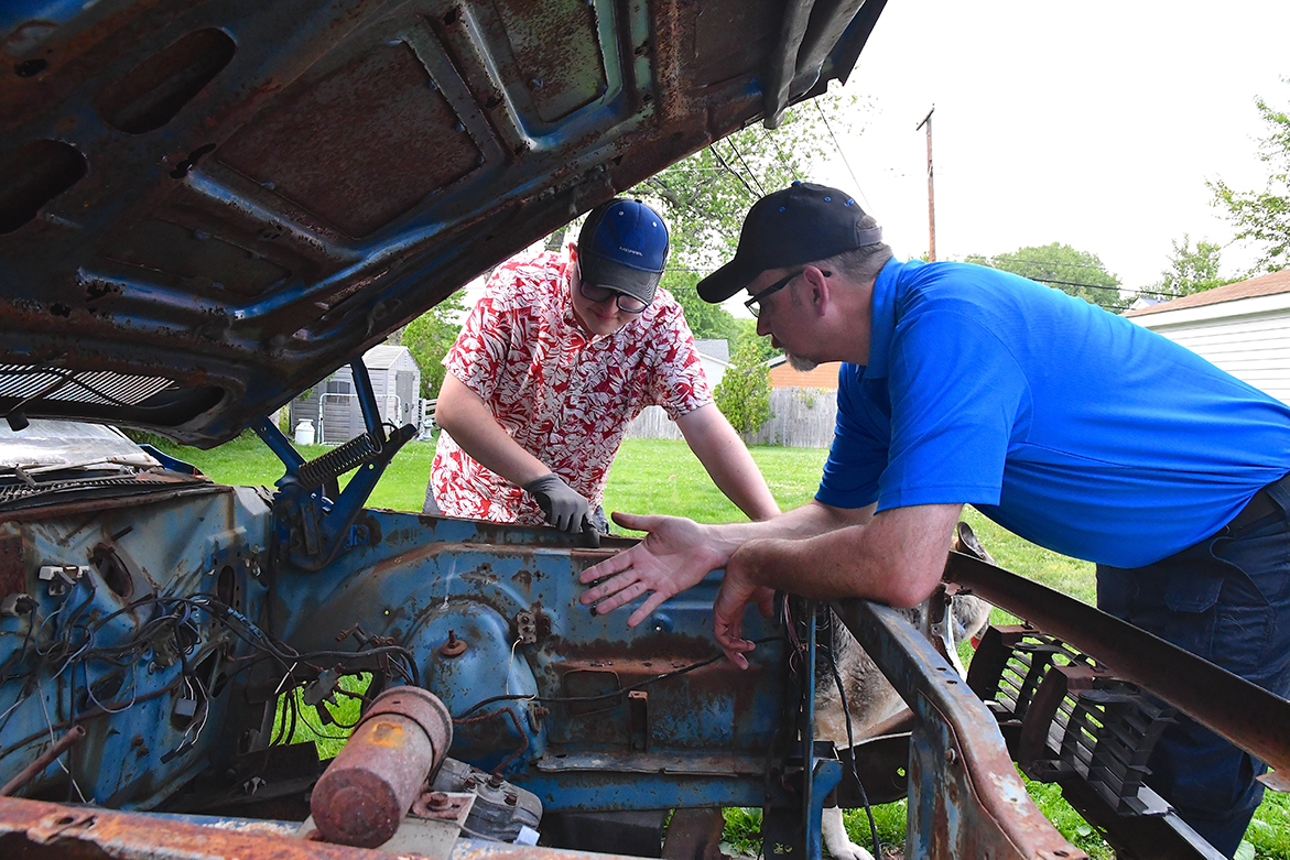 Two men looking inside an old vehicle