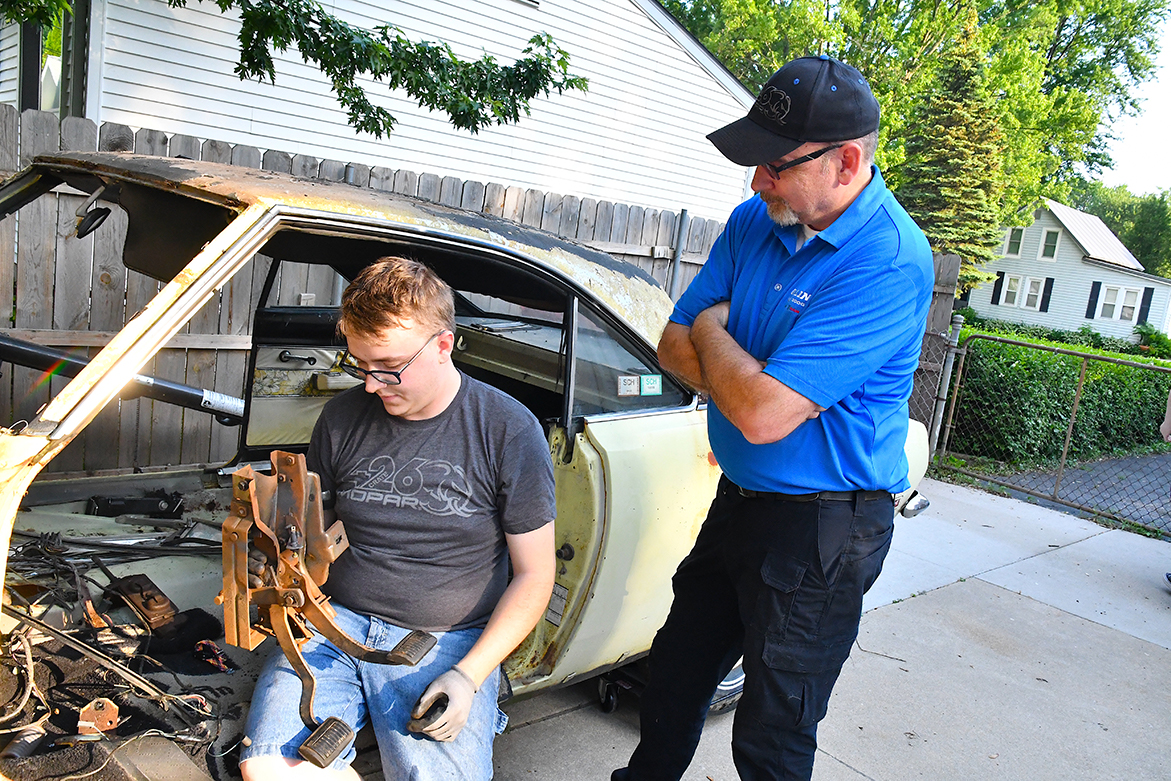 Two men inspecting rusted vehicle brakes