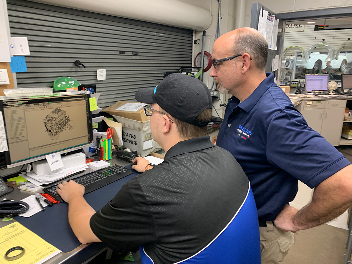 Two men looking at a vehicle engine on a computer