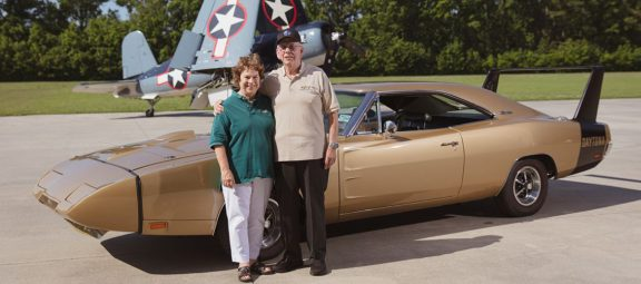 Man and woman standing with a Dodge Charger Daytona