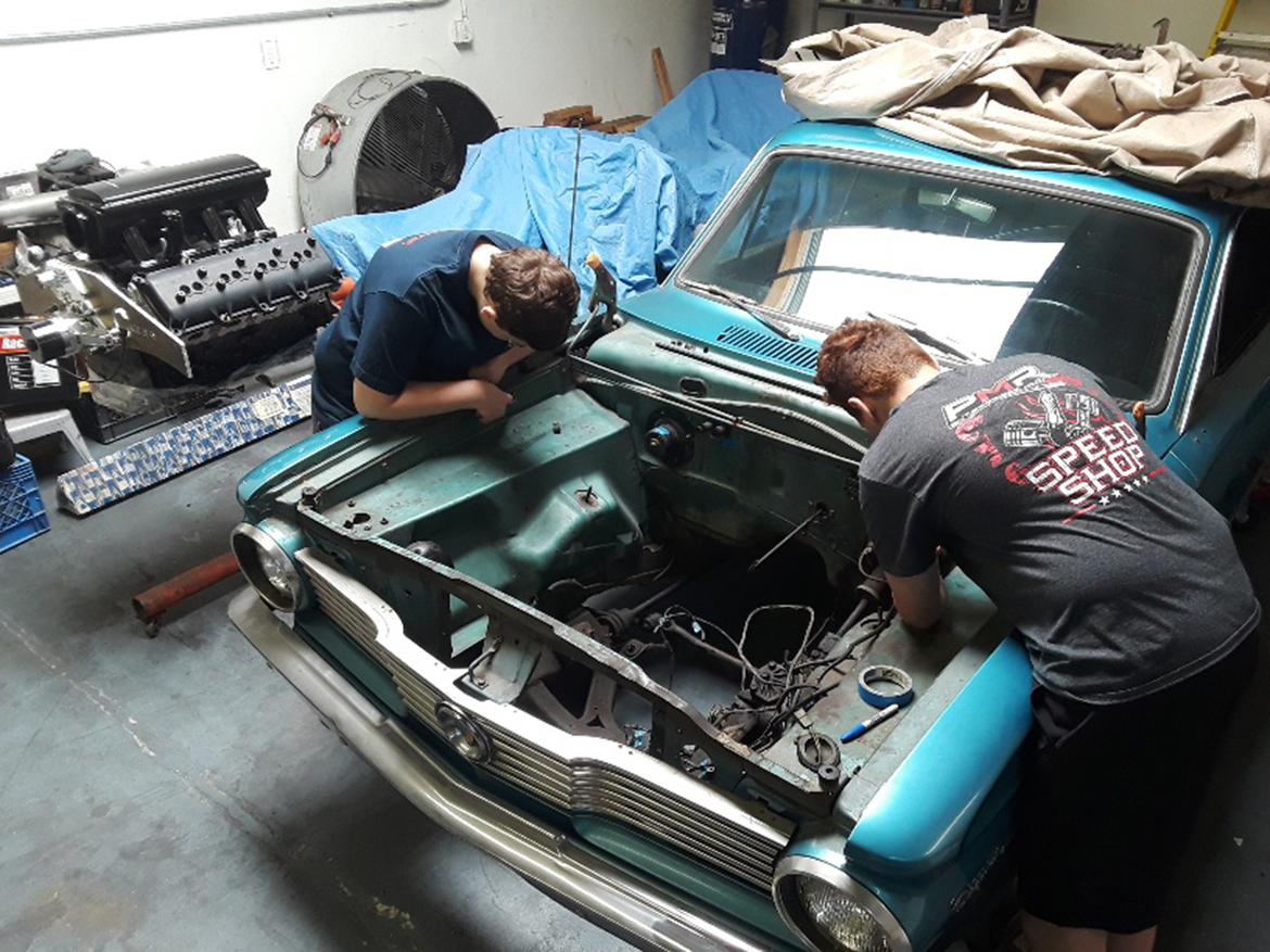 Two kids working on a vehicle engine