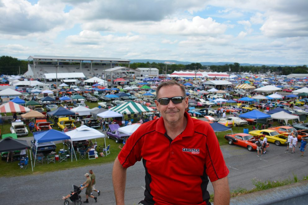 Man in front of a full lot of vehicles on display