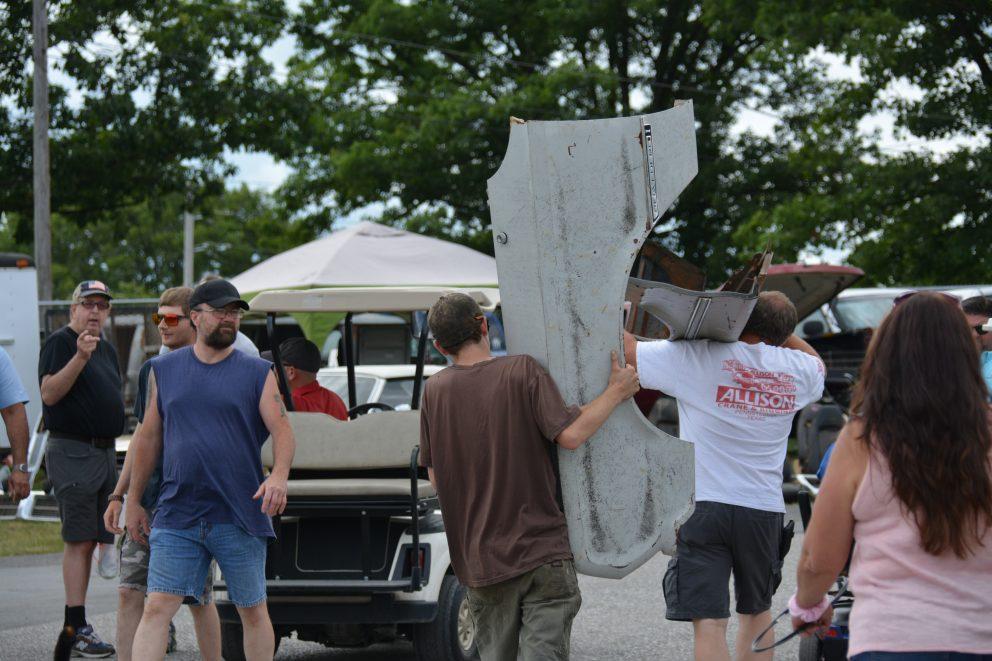 Spectators carrying a vehicle door