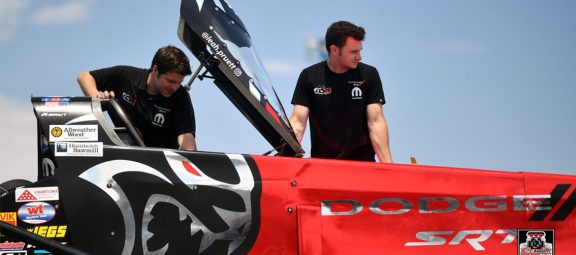 Two crew members taking a top fuel dragster out of the trailer