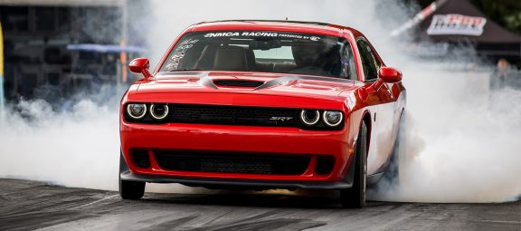 Dodge Challenger doing a burnout on a drag strip