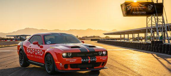 Dodge Challenger parked under a Radford Racing School sign