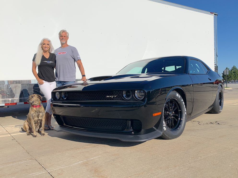 Geoff Turk and his wife standing next to his Drag Pak