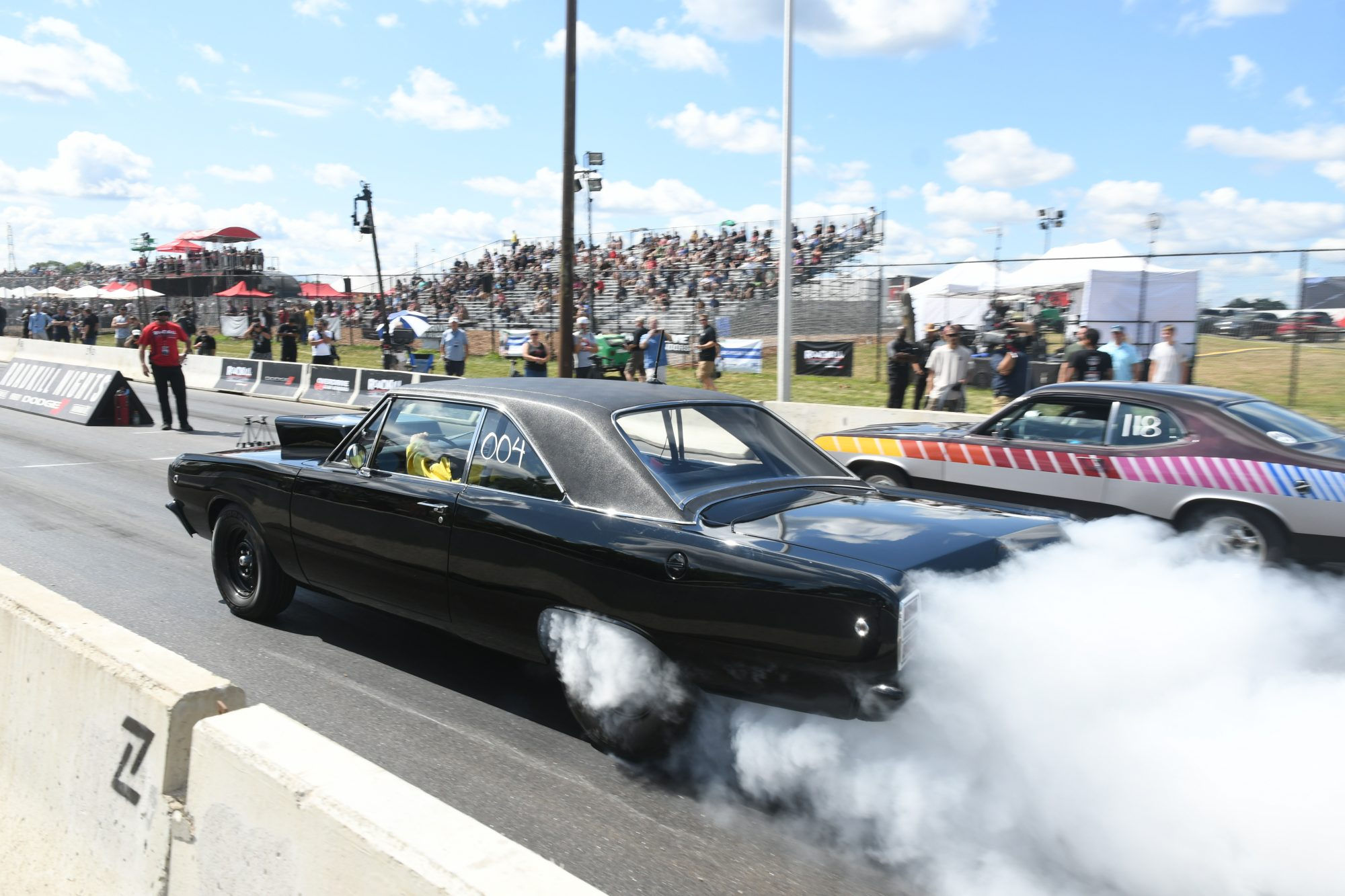 Two cars drag racing at Roadkill Nights Powered by Dodge